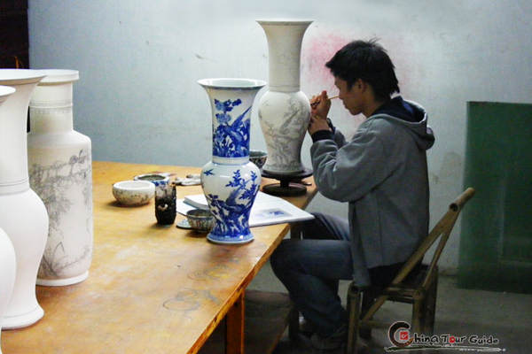 The worker is focusing on the hand-painting on the porcelains